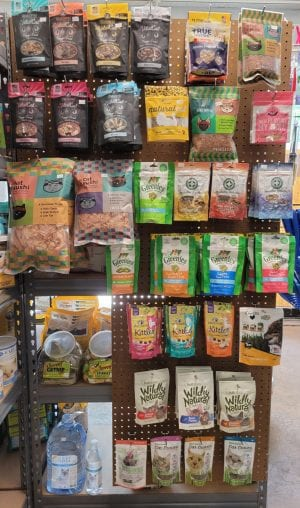 packages of pet treats hanging on a store wall